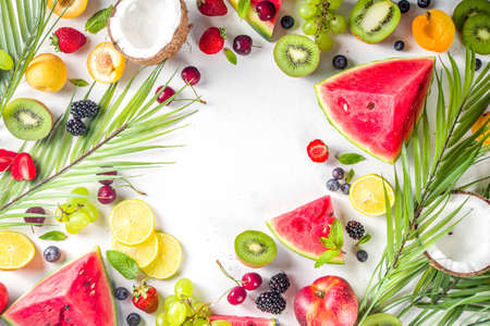 Assorted different summer tropical fresh raw fruits and berries. Clean eating, healthy lifestyle, diet and vitamin concept. Top view flatlay white table background Imagens