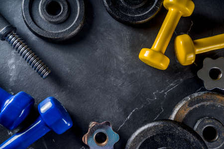 Sport and fitness concept background with dumbbells. Weight Training Equipment. Top view with space for your text, Black marble background.