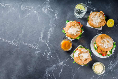 Various seafood and fish burgers assortment. Homemade healthy burger with grilled prawn, salmon, tuna, sea bass, fresh herbs, mozzarella cheese and baby spinach.