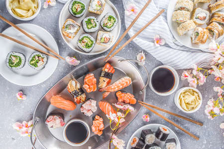 Japanese food. Big sushi set. Assorted set of various sashimi, maki and sushi rolls with different fillings - tuna, sea bass, salmon, shrimp, vegetables. Flatlay copy space