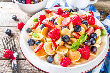 Trendy mini pancakes, Breakfast Cereal Pancakes with various summer fruit and berry Banco de Imagens