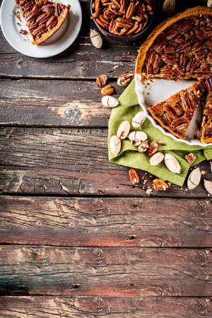 Homemade autumn pecan pie on wooden rustic background, Traditional fall and winter, thanksgiving american nut cake,