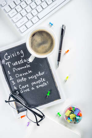 Chalk board with list of tasks, ideas, task for Giving Tuesday. Notes to various helping on Tuesday. International Charity Aid Day concept. White desktop flatlay copy space