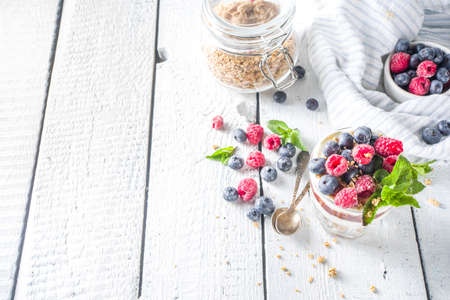 Yogurt parfafait with granola and berries. Sweet and healhty breakfast dessert in glass with granola, Yogurt, blueberries and raspberries. White wooden background top view