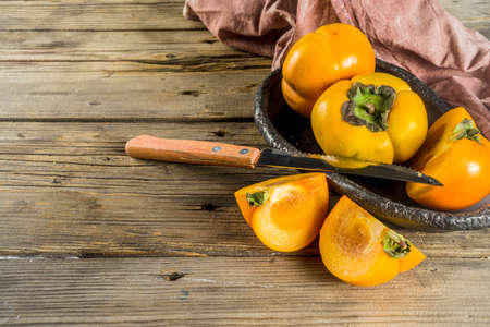 Whole and sliced persimmons, fresh organic farm fruit on rustic wooden background. Isolated, copy space Foto de archivo