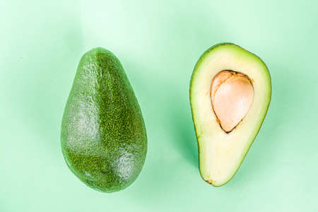Raw organic avocado, whole and sliced avocado on light green background, with green leaves, simple pattern layout, top view copy space