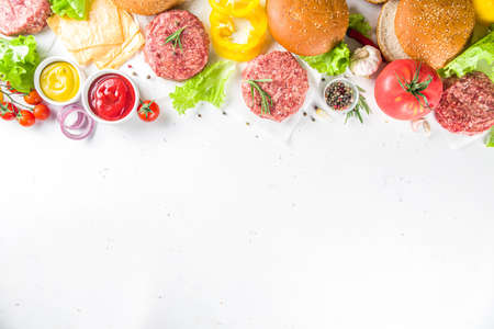 Cooking burger background. Set various cheeseburger  and beefburger ingredients - bun, tomatoes, onion, lettuce, sauces, cheese and raw burger cutlets, ready for barbecue grill. Burger bbq party fest concept, top view copy space