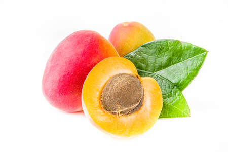 Raw whole and half sliced apricots. Fresh summer apricots fruits isolated on white background