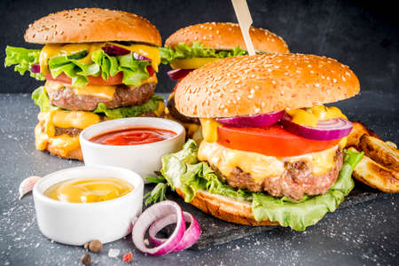 Tasty grilled homemade cheeseburgers with beef, tomato, cheese, tomato and lettuce. On dark grey background, with sauces. Top view copy space Archivio Fotografico