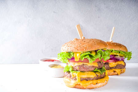 Tasty grilled homemade cheeseburgers with beef, tomato, cheese, tomato and lettuce. On white concrete background, with sauces. Top view copy space