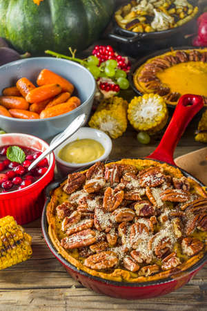 Thanksgiving family dinner setting concept. Traditional Thanksgiving day food  with turkey, green beans and mashed potatoes, stuffing, pumpkin, apple and pecan pies, rustic wooden table Foto de archivo