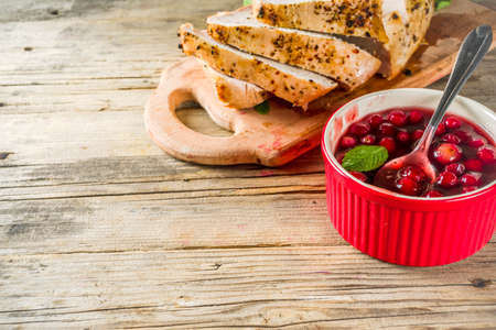 Traditional Thanksgiving autumn dish. Baked turkey breast fillet with cranberry sauce, on a cutting board wooden rustic background copy space Banque d'images