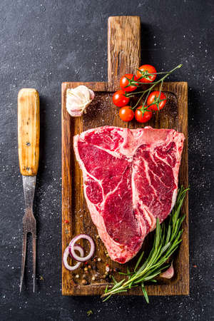 Cooking meat background. Raw aged beef t-bone steak, with spices and herbs for cooking on a gray table background top view