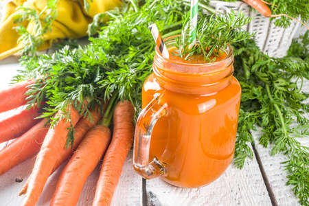 Healthy detox orange carrot smoothie or juice in mason jar on white  wooden background with fresh carrot bunch. Vegan vegetable smoothie. Stock fotó