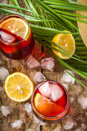 Tinto de Verano or vino de verano, Spanish Wine Cocktail. Refreshment acoholic drink sangria. Cool iced alcohol beverage with lemon juice and slices, wooden background with summer tropical decor copy space