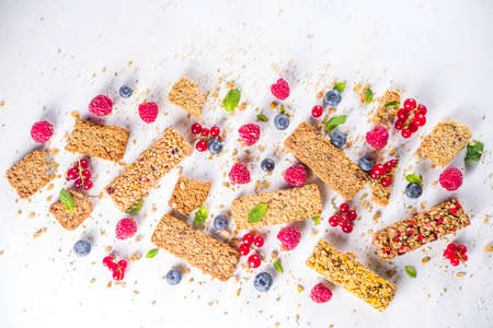 Healthy snack concept, Cereal granola bars with fresh berries and nuts on white background copy space Banque d'images
