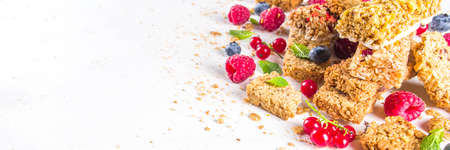 Healthy snack concept, Cereal granola bars with fresh berries and nuts on white background copy space
