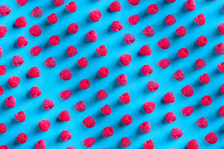 Summer berry pattern, raspberries on blue background, flatlay top view