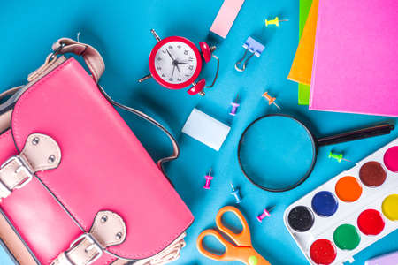 Back to school, education background. Back to School Blue Background with School Bag Backpack, Notebook, Pen, Pencil, Pencils, Magnifying Glass, Eraser, Paper Clip, Alarm Clock, School Supplies Reklamní fotografie