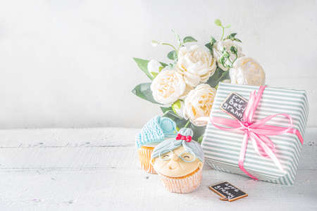 Grandparents Day holiday concept, Grandmother and Grandfather Day greeting background. Sweet homemade cupcakes for grandma and grandpa, with I love you Granny text inscription. With gifts and flowers