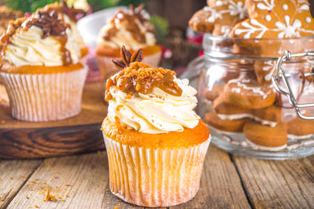 Gingerbread cupcakes with caramel sauce and spices, homemade sweet baking for Christmas, wooden background copy space Imagens