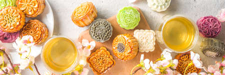 Traditional Chinese sweet dessert. Homemade Chinese snow skin and baked mooncakes, Chinese Mid-Autumn Festival food, colorful rice cakes, flatlay top view copy space