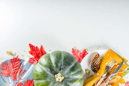 Autumn cutlery background. Fall card background for menu or invitation, banner format. With fork, knife, napkins, pumpkin, plate, multicolored leaves. On white table, top view copy space Stock Photo