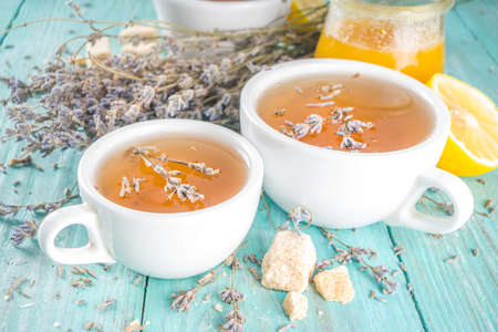 Aromatic lavender tea cup, with and bunch of lavender, honey and lemon, turquoise wooden background copy space Stok Fotoğraf