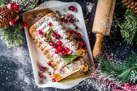 Traditional christmas baking, Festive Xmas fruitcake with dryed fruits, liquer, and cranberry decor. Homemade fruitcake on Chritmas decorated background