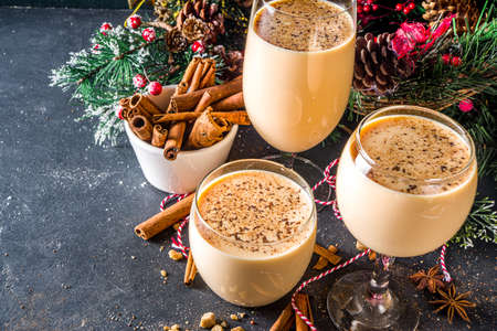 Traditional Christmas egg dairy drink with spices, in different glasses. Eggnog cocktail, Cola de mono, Crème de Vie (Cream of Life) beverage. Dark background with Christmas decor