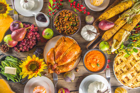 Happy Thanksgiving concept. Thanksgiving day celebration dinner setting with traditional meal and food - green beans, mashed potatoes, cranberry sauce, pumpkin soup, autumn fruits, vegetables