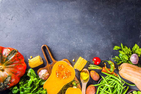 Autumn cooking background. Organic autumn harvest vegetables, raw vegan ingredients for cooking traditional thanksgiving and fall food on dark background, top view