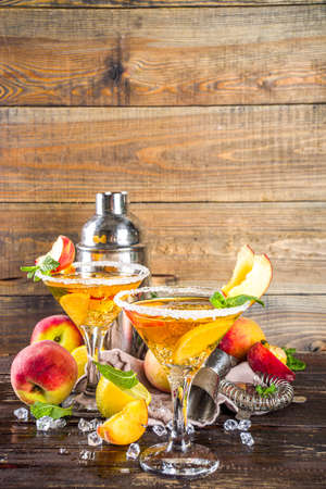 Refreshing summer drink, peach martini cocktails with gin or vodka and fresh peach garnish, wooden background copy space