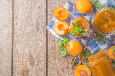 Homemade apricot jam in different jars, with fresh organic apricots on wooden rustic background copy space Banco de Imagens