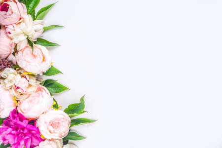 Flat lay of flowers and green leaves. Tender Peonies and chrysanthemums bloom pattern, composition for postcards on white background. Stock Photo
