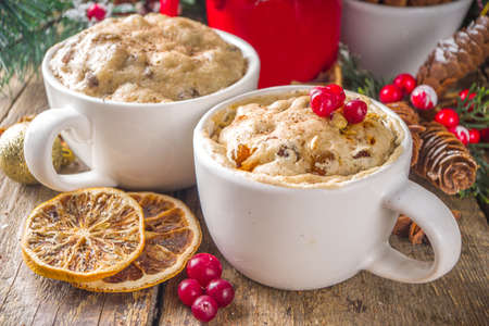 Christmas fruitcake in mug. Simple and fast recipe idea for Christmas breakfast, mug cake in microwave with traditional winter spices and fruits, on xmas decorated wooden background copy space Foto de archivo