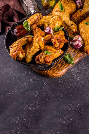 Grilled chicken legs and wings, with herbs, spices, garlic and barbeque sauce, dark concrete table background copy space top view