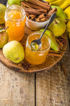 Homemade sweet and spicy pear jam. Different glass jars with pear jam, on wooden background with fresh pears and spices Stockfoto