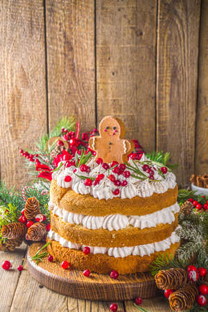 Festive Christmas gingerbread cake with whipped cream cheese, decorated cranberry and gingerbread cookies, wooden background with christmas decor copy space