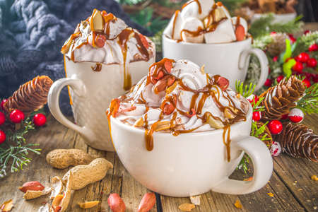 Salted Peanut Caramel Hot Chocolate. Keto and vegan hot chocolate recipe, with marshmallow and whipped coconut cream, wooden background with christmas winted decoration