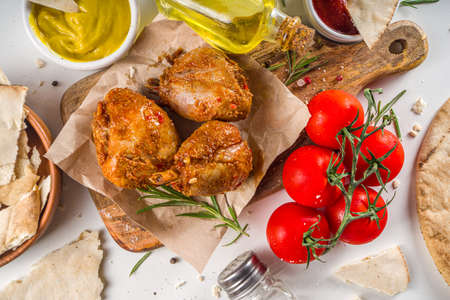 Roasted chicken legs or wings. Grill roasted spicy legs or wings, with various sauces and spices, copy space Stock Photo