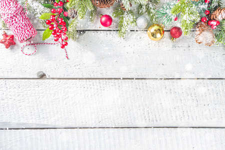 Christmas and New Year greeting card background. Xmas backdrop with fir tree branches, decoration and snowfall on wooden white board Reklamní fotografie