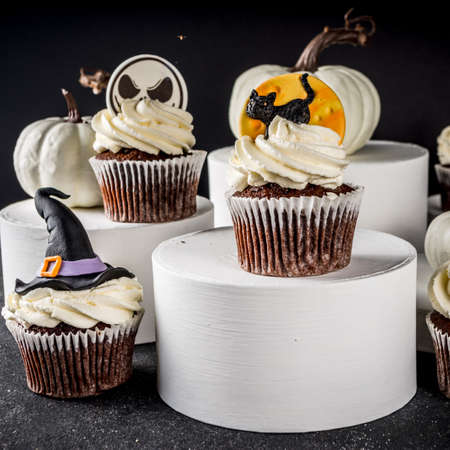 Sweets for halloween party. Funny homemade Halloween cupcakes on modern stands and podiums on dark background. Halloween party treats concept 免版税图像