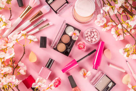 Makeup products with cosmetic bag and spring flowers. Professional Makeup set flatlay. Set of decorative cosmetics on tender pink background. Copy space above