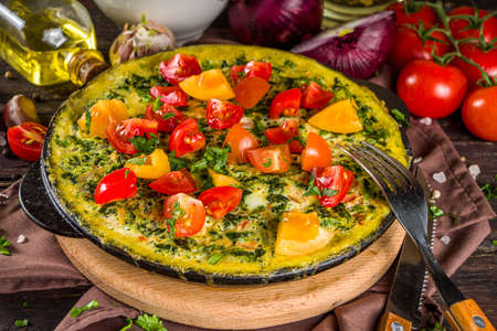 Homemade rustic style frittata. Frittata with spinach, cheese and tomato in skillet. Wooden background with vegetables copy space