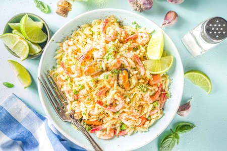 Orzo pasta with cream sauce and seafood. Homemade Orzo with various seafoods and shrimps, with lemon slices on light blue background copy space top vuew