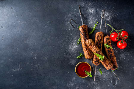 Shish kebab on skewers, from minced beef meat. Lula kebab, traditional Caucasian recipe. On black concrete background, with sauces, tomatoes and veggie salad top view copy space