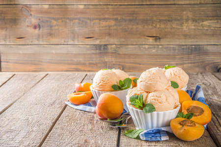 Homemade sweet apricot ice cream. Apricot gelato balls in small bowls, on wooden background with fresh apricots and mint leaves Reklamní fotografie