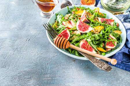 Autumn fig and arugula salad recipe. Whole vegan paleo fruit and vegetable fall salad idea. Homemade salad bowl with figs, arugula, peach and apple slices, nuts and honey. Blue concrete background copy space top vire Imagens