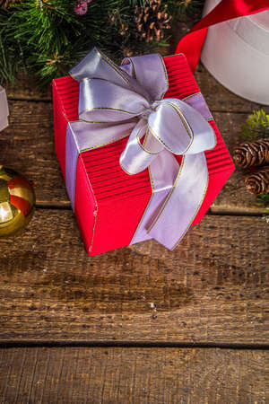 Christmas greeting card background. Many red and white gift boxes with festive ribbons, with christmas decorations and on wooden board background